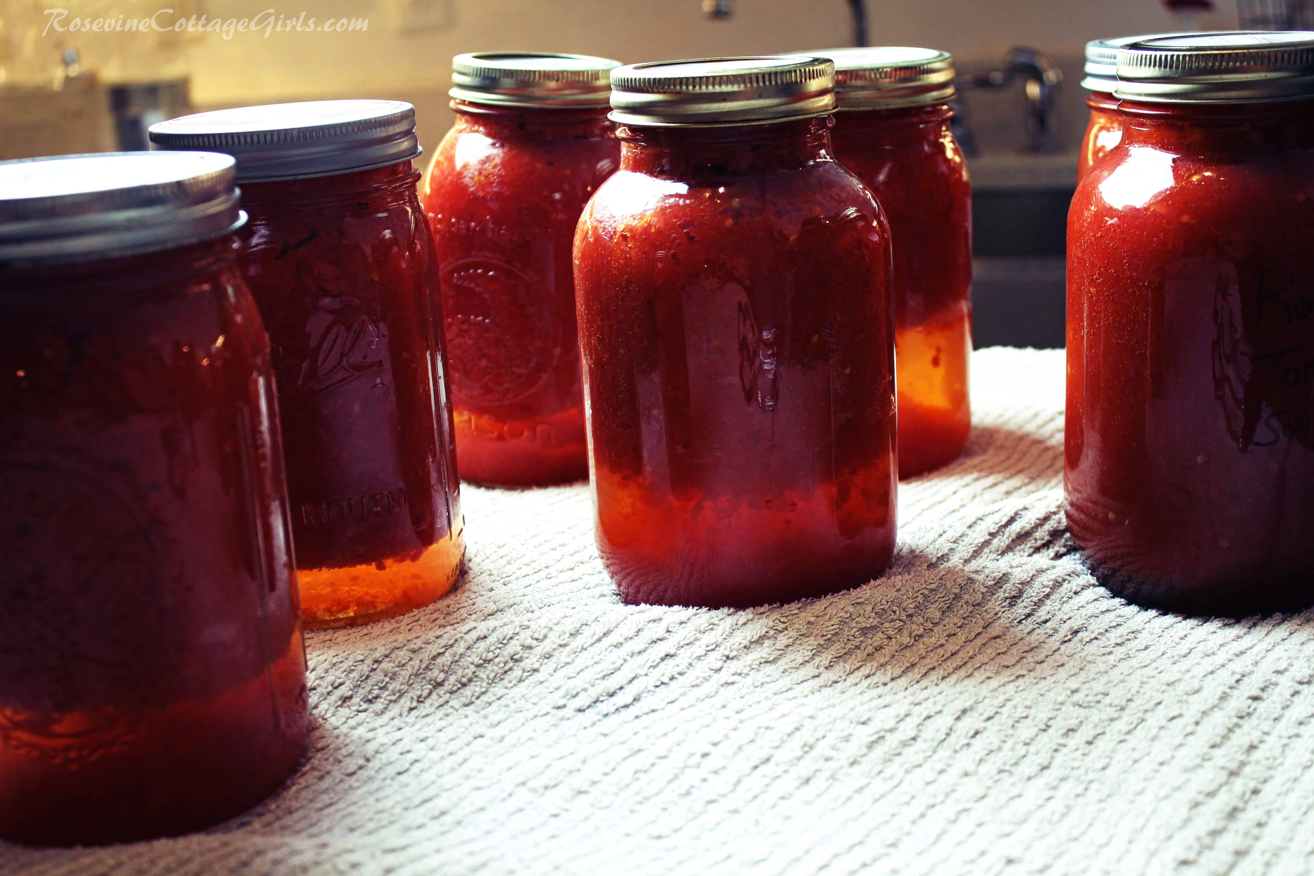 photo of jars of canned tomato sauce on a white towel | rosevinecottagegirls.com | roasted tomato sauce for canning