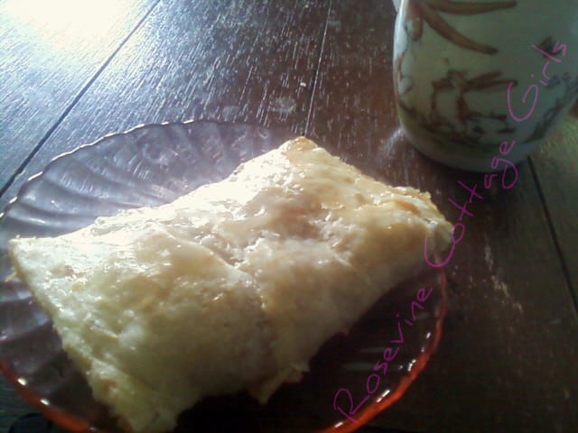 photo of an apple turnover on a pink depression glass plate on a wooden table rosevinecottagegirls.com