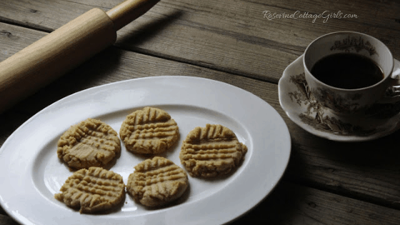 Photo of five peanut butter cookies on a white tray, a cup of black coffee half full an a wooden rolling pin | RosevineCottageGirls.com | Best Peanut Butter Cookies, Peanut Butter Cookies, Delicious Peanut Butter Cookies, by Rosevine Cottage Girls