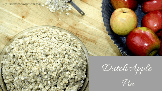 photo of a dutch apple pie on a wood background, a scoop of oats pouring out on the counter and metal container with red apples| Dutch Apple Pie by RosevineCottageGirls.com