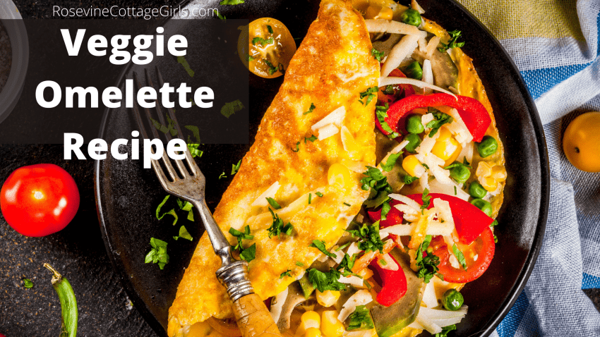 Photo of a veggie omelette on a black pate with a tomato and pepper | rosevinecottagegirls.com
