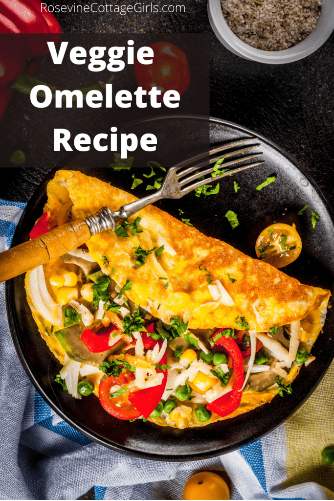 Photo of a veggie omelette with a fork on a black plate | rosevinecottage girls.com | veggie omelette, veggie omelet, vegetable omelette