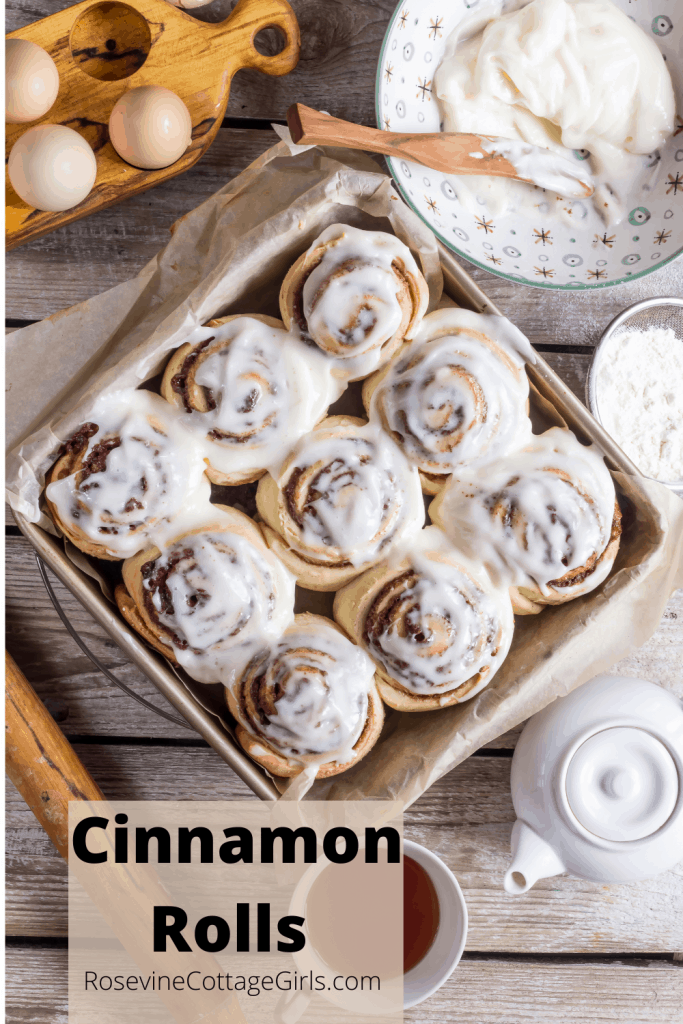 photo of a container of cinnamon roll with icing, tea pot and cup,  bowl of dough, cinnamon rolls | rosevinecottagegirls.com |