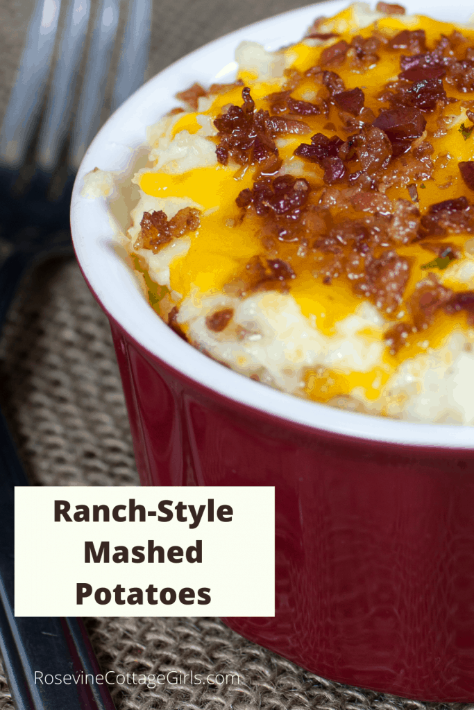 A photo of ranch-style mashed potatoes in a red bowl with melted cheese and bacon | rosevinecottagegirls.com