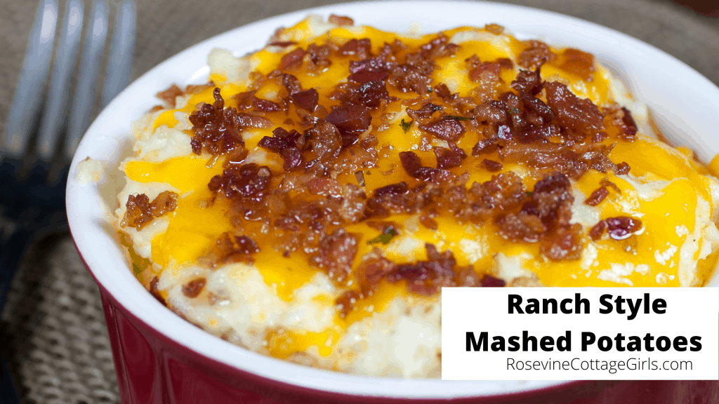A Photo of ranch-style mashed potatoes in a red bowl with bacon and cheese on it | rosevinecottagegirls.com