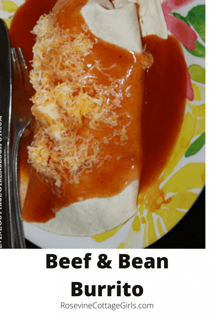 Photo of a beef and bean burrito with red sauce and shredded cheese | beef and bean burrito recipe | rosevinecottagegirls.com