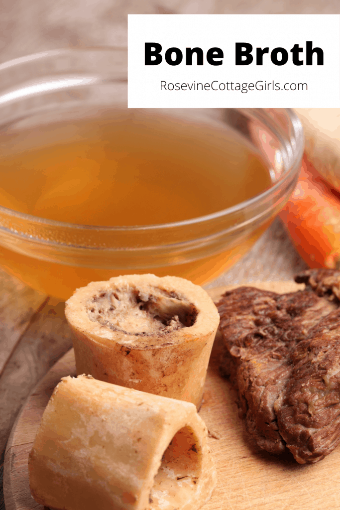 Bone Broth | photo of bone broth in a glass bowl with a cutting board with beef bones, beef and carrots sitting near it.
