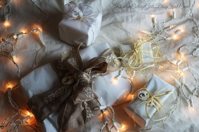 Christmas at the Cottage | photo of pretty packages wrapped up on a white blanket and white christmas lights on a string wound between them | rosevinecottagegirls.com