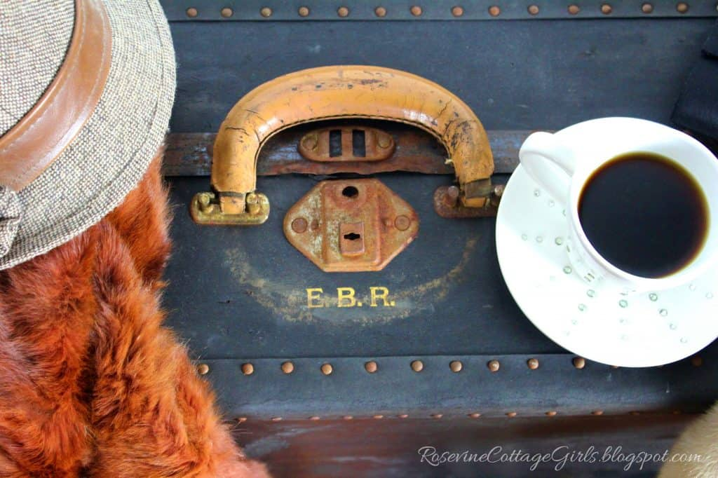 House Guests Etiquette | photo of a suitcase with a hat on top and a cup and saucer with coffee