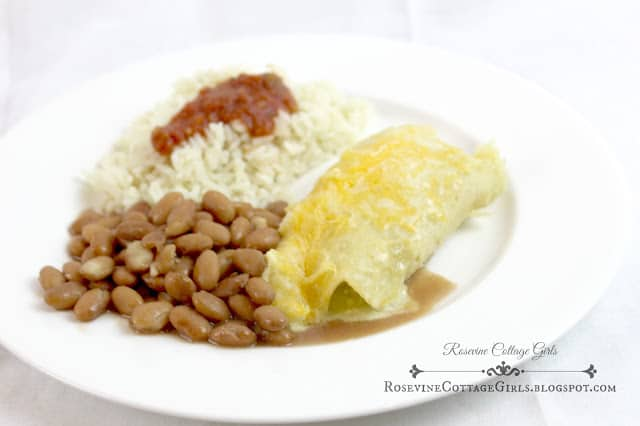 creamy chicken enchiladas with beans and rice | rosevinecottagegirls.com | white chicken enchiladas on a white plate with pinto beans and rice | white chicken enchiladas | Enchilada | creamy chicken enchiladas | rosevinecottagegirls.com
