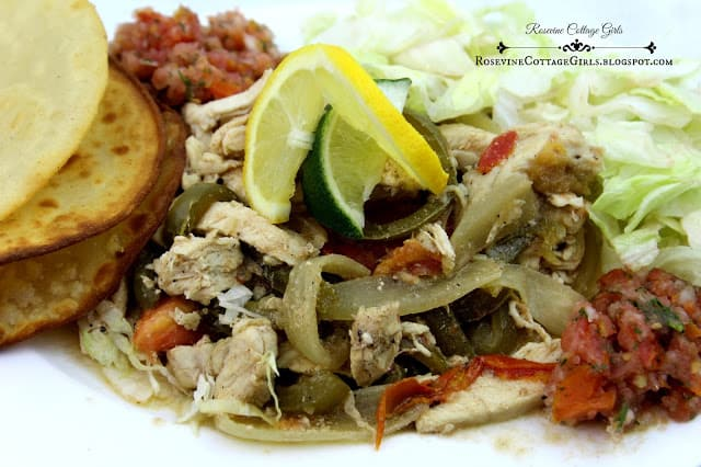Chicken Fajitas on a white platter with wedges of lemons and lime by rosevinecottagegirls.com