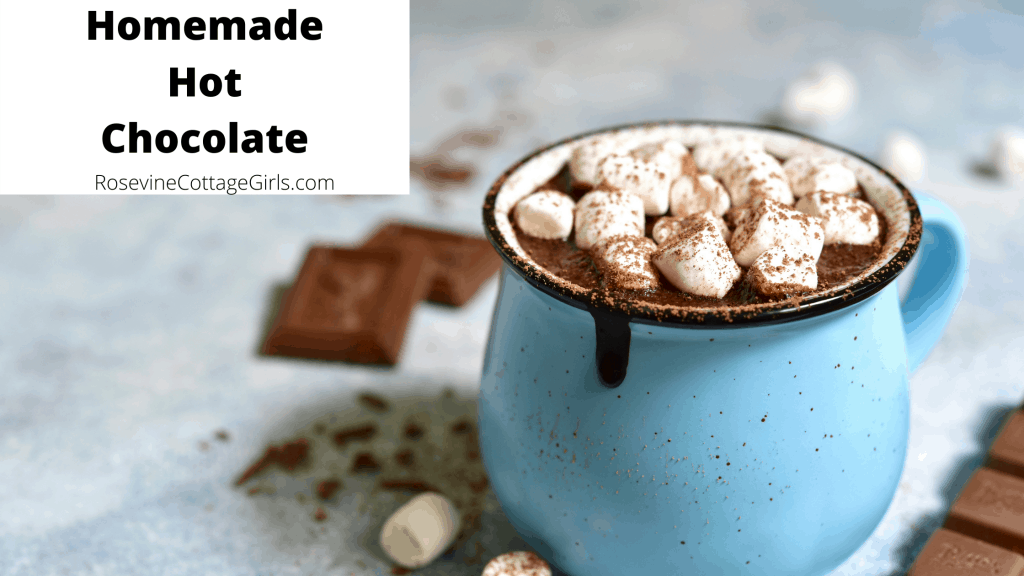 a blue and black mug filled with homemade hot chocolate and marshmallows and bars of chocolate sitting behind it | RosevineCottageGirls.com