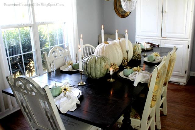 Farmhouse Thanksgiving Tablescape by RosevineCottageGirls.com | Green and white pumpkins on a table with candles set for dinner with plates by rosevinecottagegirls.com