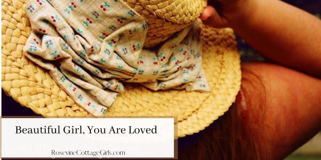 beautiful girl, you are loved | woman facing away from camera with a large straw hat on.