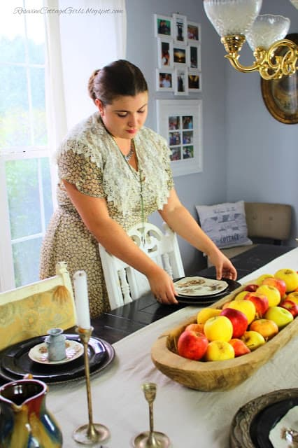 photo of young woman setting a dining table decorated with brown and white plates, wooden chargers, a beige table runner with a wooden bread dough bowl filled with pretty red and yellow apples on a black table | simple apple tablescape | simple fall decorating | by rosevinecottagegirls.com