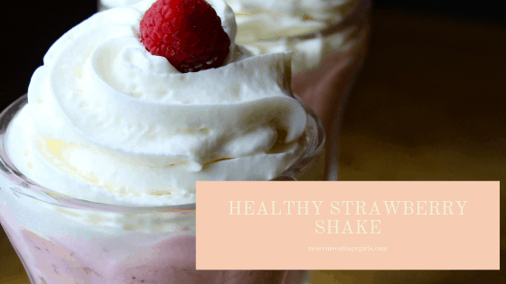 healthy strawberry shake | Ice cream sundae cup with a healthy strawberry shake topped with whipped cream and fresh raspberry | strawberry shake | Rosevine Cottage Girls photo | rosevinecottagegirls.com
