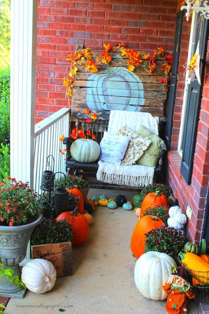 photo of a front porch decorated for fall with mums, pumpkins, a blanket on bench and colorful garland. (c) rosevine cottage girls Decorating a narrow porch for fall #RosevineCottageGirls Decor For Small Front Porch