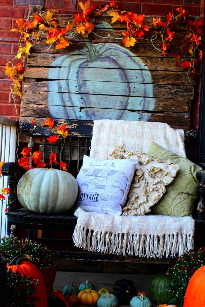 Gorgeous fall front porch from the Rosevine Cottage Girls Decor For Small Front Porch - (c) Rosevine Cottage Girls | black bench with pillows and blanket. Pumpkins and wooden picture with blue pumpkin on it and colorful garland.