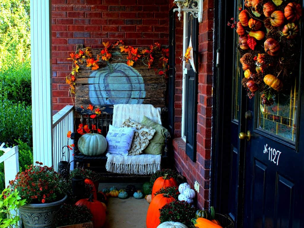 How to decorate a narrow front porch for fall #RosevineCottageGirls Decor For Small Front Porch (c) rosevine cottage girls | Beautiful porch decorated for fall with mums in pots and pumpkins around a black bench with pillows and a warm blanket