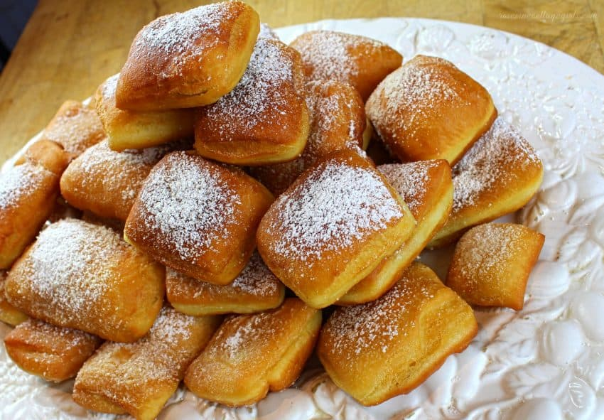 Platter of fried beignet on a white platter sprinkled with powdered sugar | rosevinecottagegirls.com |The best beignet recipe that you'll ever try! Slight crunch on the outside and soft on the inside.