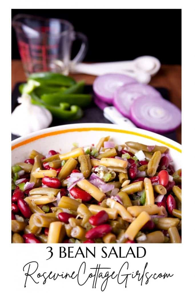 three bean salad   a bowl of pickled 3 bean salad and cutting board with sliced onions peppers and garlic cloves