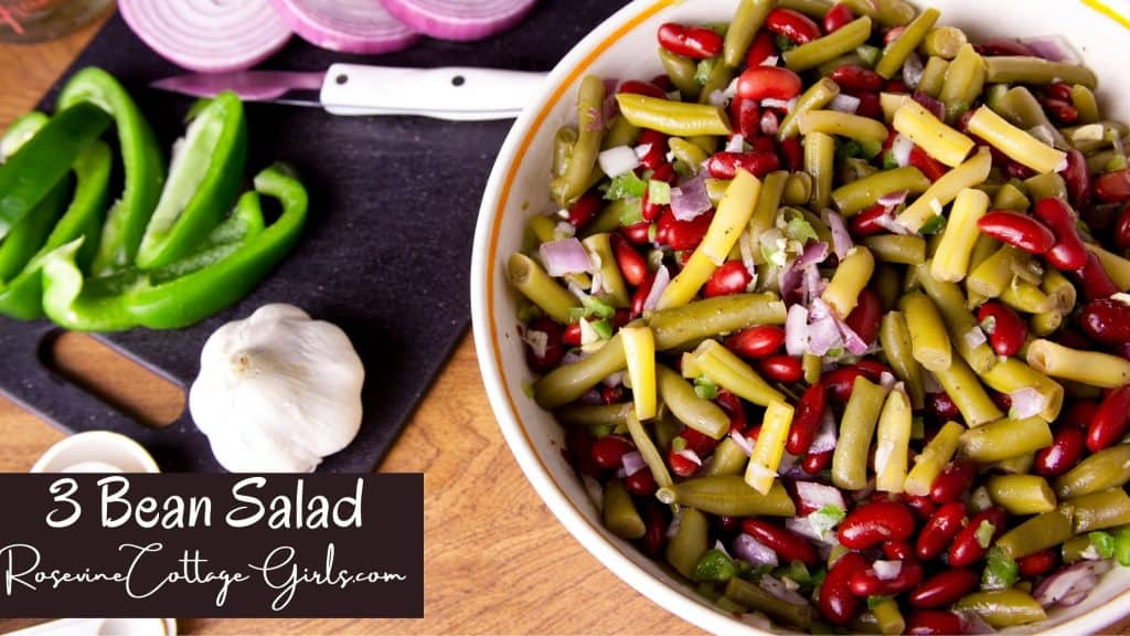 three bean salad | photo of a bowl filled with three bean salad and a cutting board with onion, garlic and green peppers