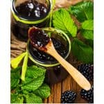 Blackberry Preserves | two canning jars with blackberry preserves and blackberry leaves on the counter